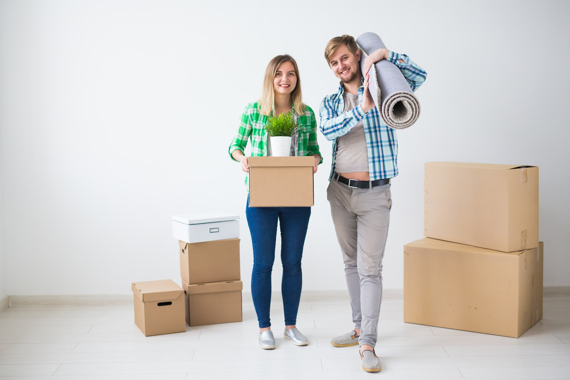 Family, new apartment and relocation concept - Young couple moving in new house