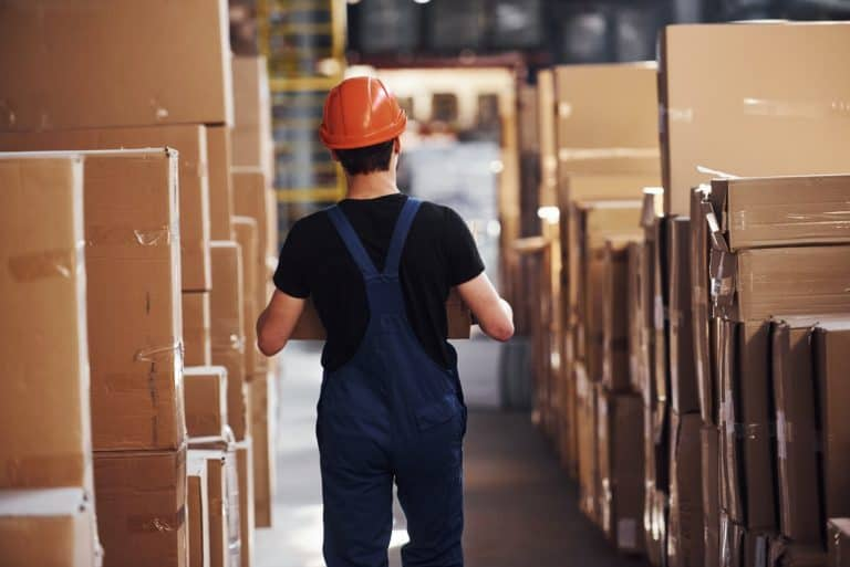 Young storage worker in uniform and hard hat carries box in hands